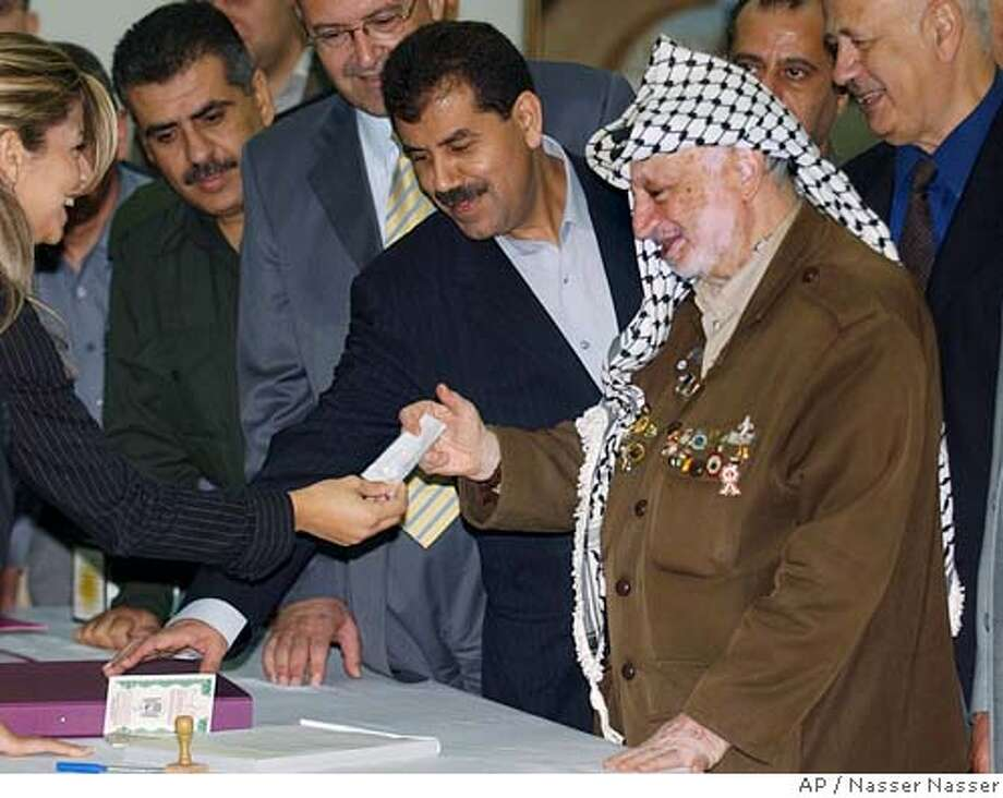 Palestinian leader Yasser Arafat receives his voter registration card after opening a voter registration drive at a polling station at his headquarters in the West Bank town of Ramallah, Saturday, Sept. 4, 2004. Palestinians launched a voter registration drive Saturday, a first step toward long-overdue elections, and Arafat promised that voting for parliament and president would take place this winter. (AP Photo/Nasser Nasser) Photo: NASSER NASSER