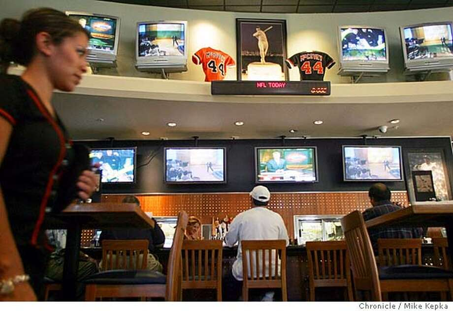 A.J. Carillo of Pleasant Hill (center at bar) tries to pick a TV to watch at McCovey's.  McCovey's in Walnut Creek has 26 TVs including one in each bathroom.  MIKE KEPKA/The Chronicle Photo: MIKE KEPKA