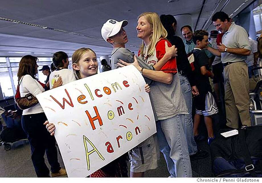 9 yr old Daniell holds the sign she showed to her brother as he came in after customs. Her bro is in gray behind her, Aaron Cutts age 13 as he gives mom, Lynn a hug. Young baseball players from San Mateo arrive back from visit to sister city in Japan. this all-star team rep'd the city of San Mateo in a cultural exchange program. They arrive at SFO and greeted by parents. 8/19/05 in San Francisco.  Penni Gladstone / The Chronicle Photo: Penni Gladstone