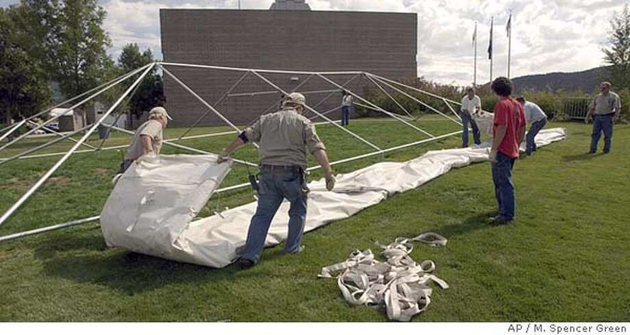 Eagle Co. Facility Management employees take down a media work tent outside the Justice Center Thursday, Sept. 2, 2004 in Eagle, Colo. where the Kobe Bryant sexual assault case was to begin next week. Bryant's case was dismissed without the possibility of being refiled yesterday, Wednesday, Sept. 1, 2004. (AP Photo/M. Spencer Green) Photo: M. SPENCER GREEN