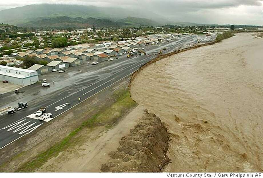The rain-swollen Santa Clara River is rapidly eroding land the Santa Paula Airport sits on, Tuesday, Feb. 22, 2005, in Santa Paula, Calif. A day earlier the bank ran in a straight line from the bottom middle to the trees on the top right. (AP Photo/Ventura County Star, Gary Phelps) LOS ANGELES TIMES OUT LOS ANGELES DAILY NEWS OUT MAGS OUT Photo: GARY PHELPS