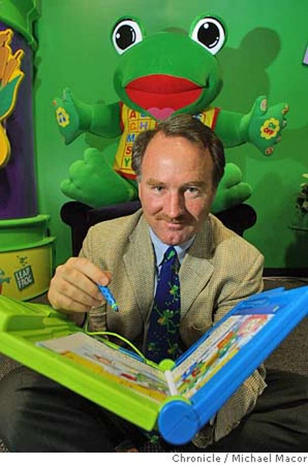 """LEAPFROG1-C-26JUL01-BU-MAC Emeryvilee based """"Leap Frog"""" educational toy company. Company President of """"LeapFrog"""", Michael Wood with the """"LeapPad"""", their hottest selling product. The educational reading toy magically brings real paper books to life.The company's main character """"leap"""" looks over Woods shoulder. by Michael Macor/The Chronicle CAT Photo: MICHAEL MACOR"""