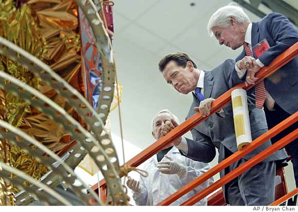 Gov. Arnold Schwarzenegger, center, examines a Defense Support Program satellite with U.S. House Appropriations Chair Rep. Jerry Lewis, right R-Calif., at the Northrop Grumman plant in Redondo Beach, Calif., on Tuesday, Feb 22, 2005. Northrup Grumman technician Bobby Kubiciak is at left. Schwarzenegger, Lewis and Rep. Jane Harman, D.Calif., toured the plant and nearby Los Angeles Air Force Base. (AP Photo/Bryan Chan, Pool)