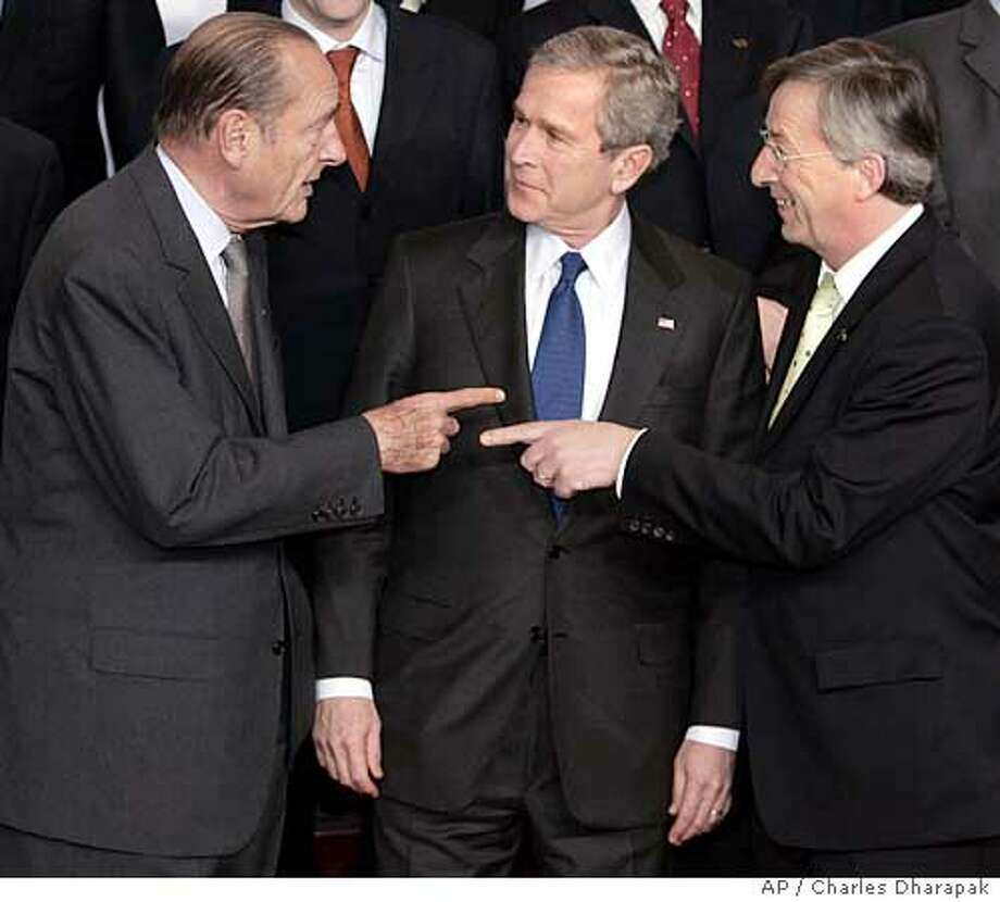 U.S. President Bush, center, looks on as French President Jacques Chirac, left, and European Union President and Prime Minister of Luxembourg Jean-Claude Juncker, point to eachother during a family photo with European Union leaders in Brussels, Belgium, Tuesday, Feb. 22, 2005. The 25 European leaders met with Bush at the EU headquarters after two years of intense disagreements, notably over the Iraq war. (AP Photo/Charles Dharapak) Ran on: 02-23-2005  President Bush (center) listens as French President Jacques Chirac (left) and European Union President and Prime Minister of Luxembourg Jean-Claude Juncker share points during a photo session with European Union leaders in Brussels. Ran on: 02-23-2005  President Bush (center) listens as French President Jacques Chirac (left) and European Union President and Prime Minister of Luxembourg Jean-Claude Juncker share points during a photo session with European Union leaders in Brussels. Photo: CHARLES DHARAPAK
