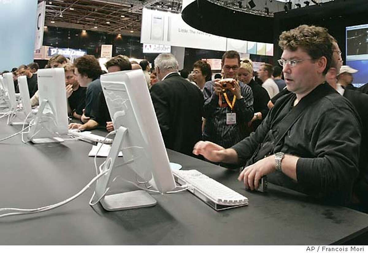 A visitor at the Apple Expo looks at the iMac G5, a new system that features a G5 processor and a new design that integrates the entire computer right into the flat panel display, in ParisTuesday, Aug. 31, 2004. The Apple Expo opened Tuesday and runs through Sept. 4. iMac G5 Systems are expected to begin shipping in mid-September. (AP Photo/Francois Mori)