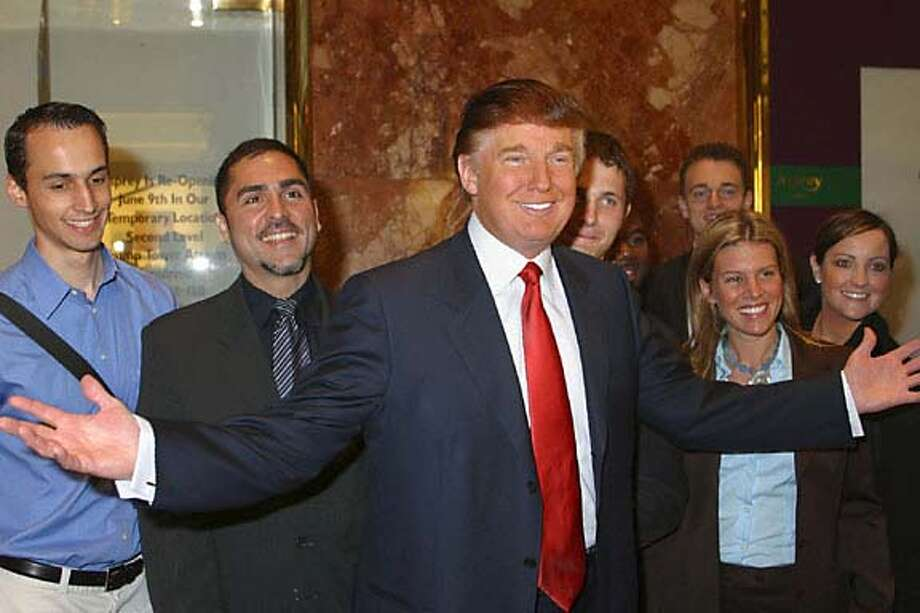 "**FILE** Donald Trump poses with prospective contestants during an audition for NBC's reality series ""The Apprentice,"" in this undated publicity photo. The real estate titan is coming out with a new book. ""How to Get Rich'' will be published by Random House in April, coinciding with the live finale of ""The Apprentice.'' In ""The Apprentice,'' which debuted earlier this month, would-be moguls vie for Trump's favor and ""the dream job of a lifetime'' as his yearlong protege. (AP Photo/NBC, Eric Liebowitz) Photo: ERIC LIEBOWITZ"