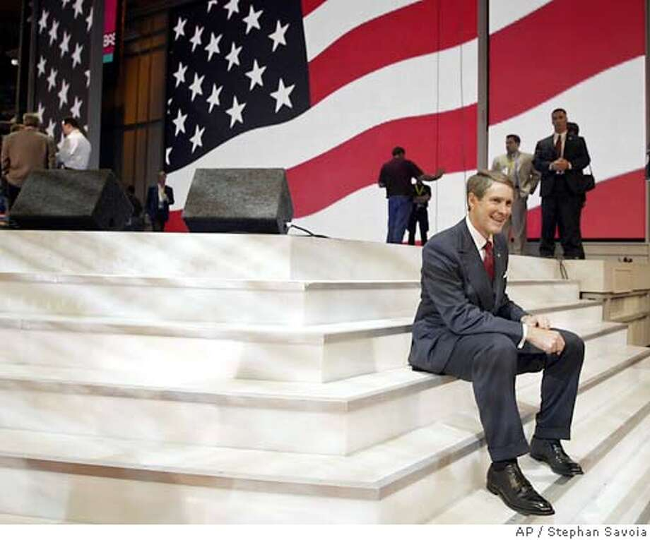 Senate Majority Leader Bill Frist sits on the steps to the stage as a photographer takes his picture after a sound check in preparation for the Republican National Convention in New York, Sunday, Aug. 29, 2004. The convention begins Monday. (AP Photo/Stephan Savoia) Photo: STEPHAN SAVOIA