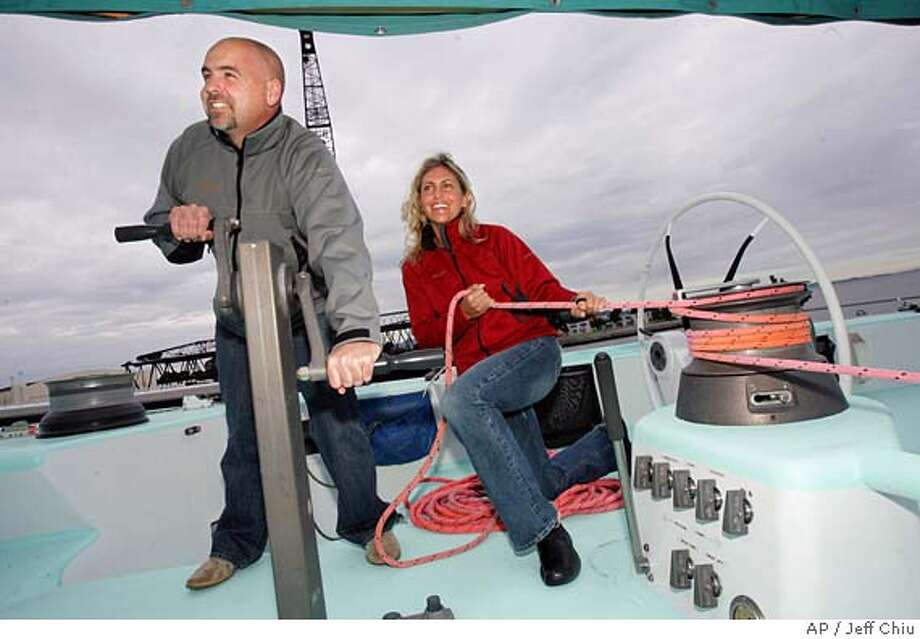 John Sweeney and Tina Kleinjan of the Sausilito Challenge 2007 crew are photographed aboard one of the America's Cup boats in Treasure Island, Calif., on Thursday, Feb. 17, 2005. The Sausalito Challenge is offering a spot on its boat to the most qualified person willing to pay a ''participation fee'' of at least 10 million euro, approximately $13 million. (AP Photo/Jeff Chiu) Photo: JEFF CHIU