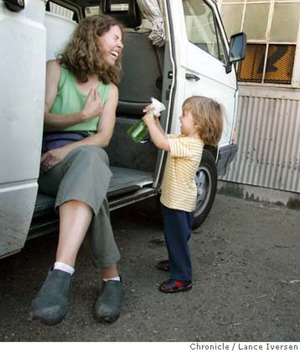 BURNINGKIDSXX_0108_LI.JPG Helen Alvarez gets sprayed with water by her son Felix Harth (cq) age 2 from Berkeley, outside the American Steal Warehouse in Oakland. The warehouse is being used to construct a children�s all steal structure for a children�s play ground at Burning Man on the Black Rock Desert in Nevada this year. Burning Man is earning a new reputation as a sort of desert Disneyland as more and more families from the Bay Area and beyond is hauling the kiddies out to Black Rock City. It was probably inevitable. The Burners, who got their start on a San Francisco beach, are growing up and having kids but don't want to stop frolicking in the desert. They say it's a great place for kids to express themselves and experience interactive art, as long as they can manage the heat, the dust storms and the occasional downpour. And they say the sex and drugs, while certainly there, are avoidable. And seeing naked people never really hurt anyone. By Lance Iversen/San Francisco Chronicle