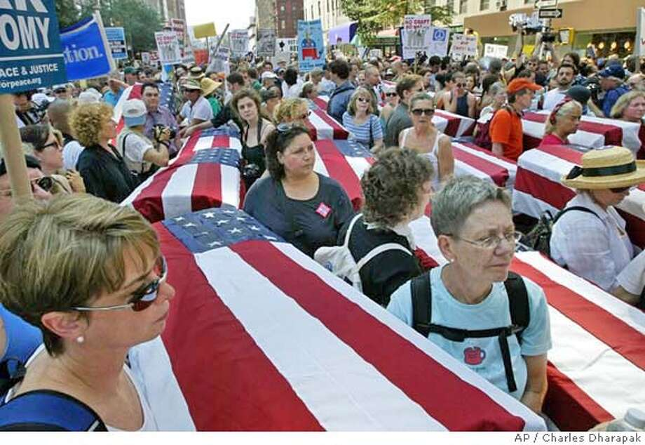 Protestors march with part of a group of mock coffins signifying American soldiers who have died in Irag during a protest march leading up to the Republican National Convention, sponsored by United for Peace and Justice, in New York, Sunday, Aug. 29, 2004. The Republican National Convention is scheduled to begin Monday. (AP Photo/Charles Dharapak ) Photo: CHARLES DHARAPAK