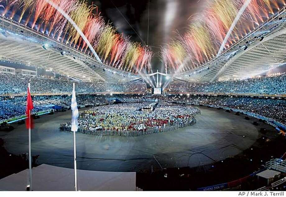 Fireworks explode as the Chinese and Greek flags fly during the closing ceremony of the 2004 Summer Olympics in Athens, Sunday, Aug. 29, 2004. (AP Photo/Mark Terrill) Photo: MARK TERRILL
