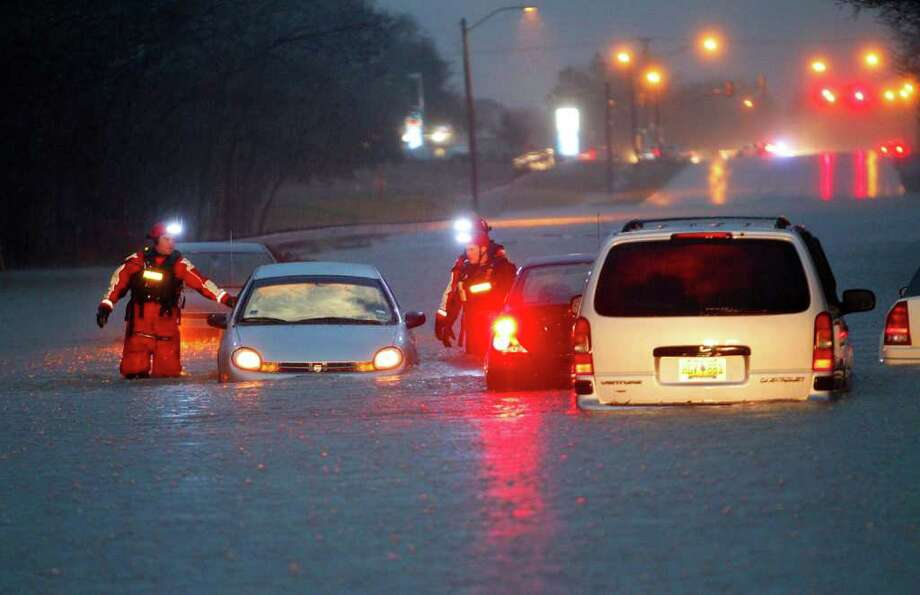Members of Fort Worth's Swift Water Rescue Team check on vehicles that were left stalled on the city's Trinity Boulevard. Photo: Dallas Morning News, Tom Fox