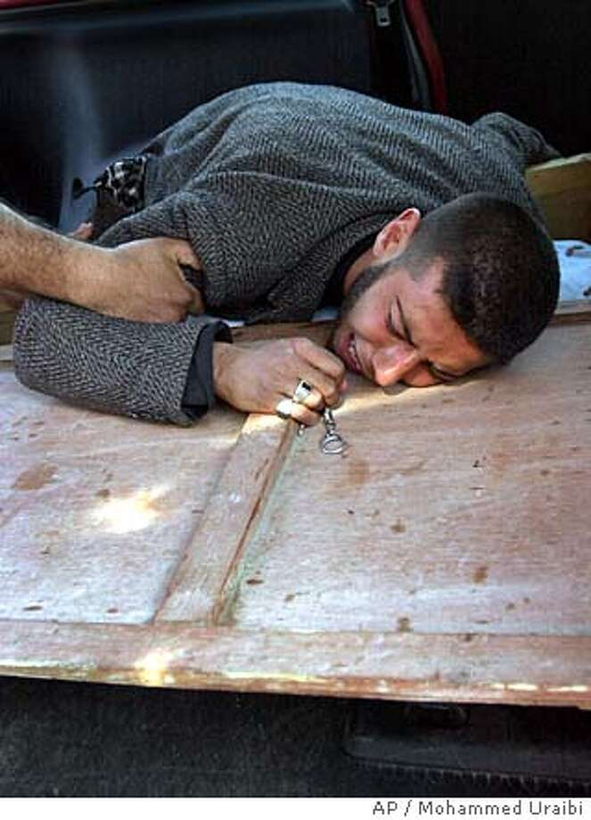 Aqil, who wanted only to give his first name, cries in grief on the lid of his brother Abu-Zainab's coffin at the al-Yarmouk hospital, who is a victim of a suicide bomb-blast at the al-Khadimain mosque in the Dora neighbourhood of Baghdad, Iraq Friday, Feb. 18, 2005. Three explosions aimed at Shiite worshipers ripped through Baghdad during Friday prayers and killed more than a dozen people and injured dozens, officials said, on the eve of Shiite Islam's most important holiday of Ashoura. (AP Photo/Mohammed Uraibi) Photo: MOHAMMED URAIBI
