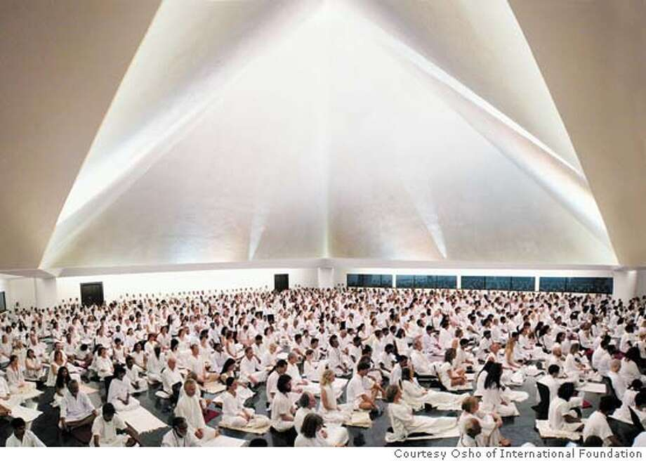 "Beloveds gather in Osho Auditorium for the nightly Osho White-Robe Brotherhood meditation. The meditation involves four parts: wild dancing, silence, ""Gibberish and Let-Go"", and watching a video of Osho."