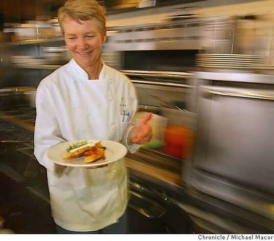 "Somerville moves through the kitchen at warp speed with a plate of ""Crostini"", Mequite grilled Italian bread with peperonata with capers and basil; picholine olive tapenade; fromage blanc and chives. Profile of Executive Chef Annie Somerville of, ""Greens' Restaurant. Somerville has worked for the past 23 years at, ""Greens"" which is located in Building A at Fort Mason. 8/5/04 in San Francisco Michael Macor/San Francisco Chronicle Photo: Michael Macor"