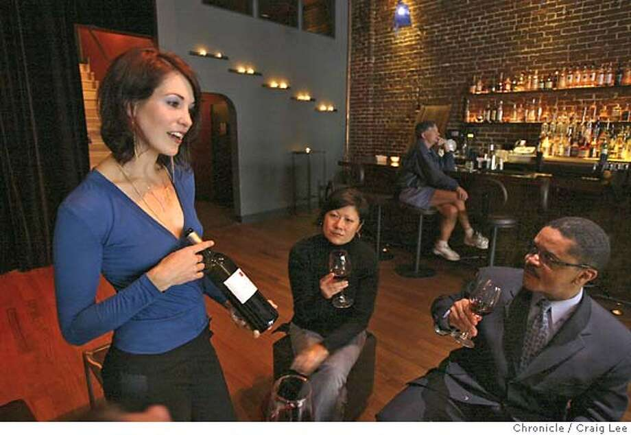 "Story on the ""new sommelier"" for the magazine. Photo of Nicole Burke (left), 31, sommelier and wine buyer at Swig, a new nightclub on Geary near Taylor street. Formerly called was the location of the Blue Lamp. The people seated to the right of Nicole Burke are Yuni Chi (middle) and George Powell (right). Event on 7/26/04 in San Francisco. Craig Lee / The Chronicle Photo: Craig Lee"