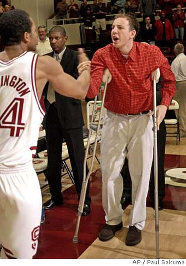 Injured Stanford guard Dan Grunfeld uses crutches as he shakes hands with forward Fred Washington, left, before Stanford's game against Southern California, Thursday, Feb. 17, 2005, in Stanford, Calif. Grunfeld suffered a torn anterior cruciate ligament in his right knee on Saturday and will miss the remainder of the season. (AP Photo/Paul Sakuma) Photo: PAUL SAKUMA