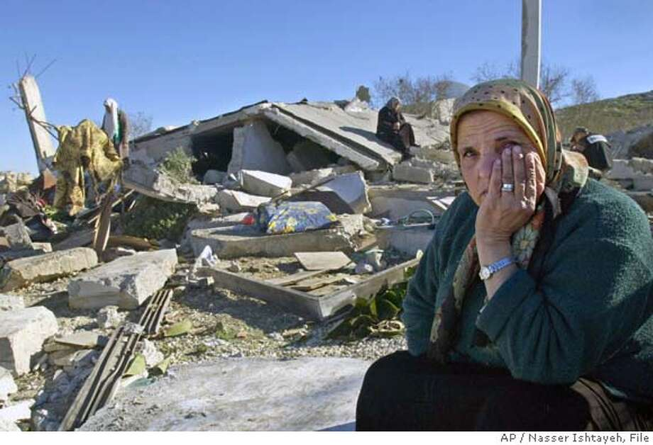 ** FILE ** Palestinian Jamila Abu Aisheh sits next to the demolished former house of her niece Darin, a female suicide bomber, after it was destroyed by Israeli soldiers in this Jan. 10, 2003 file photo in the village of Beit Wazzin on the outskirts of the West Bank town of Nablus. Darin Abu Aisheh blew herself up at an Israeli military checkpoint on February 2002 and wounded three policemen. Israel's defense minister ordered Thursday, Feb. 17, 2005 an end to the army's practice of demolishing the houses of Palestinian attackers. Earlier military officials said an Israeli army committee investigating Israel's policy of demolishing houses belonging to the families' of suicide bombers said the policy inflamed Palestinian hatred and should be stopped. (AP Photo/Nasser Ishtayeh) Photo: NASSER ISHTAYEH