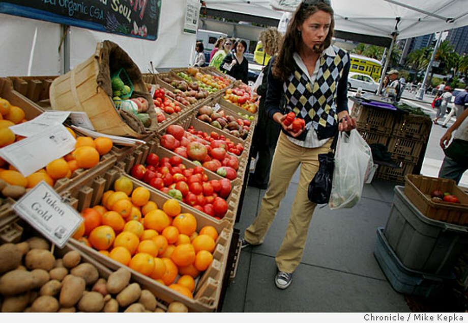 "Lorian Newcomer of North Beach, who wears what she called her ""standard preppie outfit,"" picked up a few fresh tomatoes for dinner on break from her job at Gap Inc., just a few blocks away. Chronicle photo by Mike Kepka"