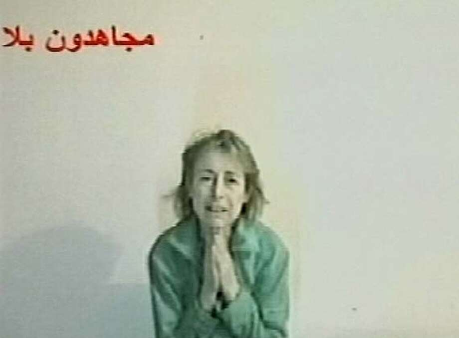 "A frame grab taken from a video tape released by insurgents February 16, 2005, shows Giuliana Sgrena, an Italian journalist kidnapped in Iraq, begging for her life and appealing for foreign troops to withdraw from Iraq. ""I beg you, put an end to the occupation. I beg the Italian government and the Italian people to put pressure on the government to pull out,"" she said on the undated tape, holding her hands in front of her in supplication. REUTERS/Handout Photo: HO"