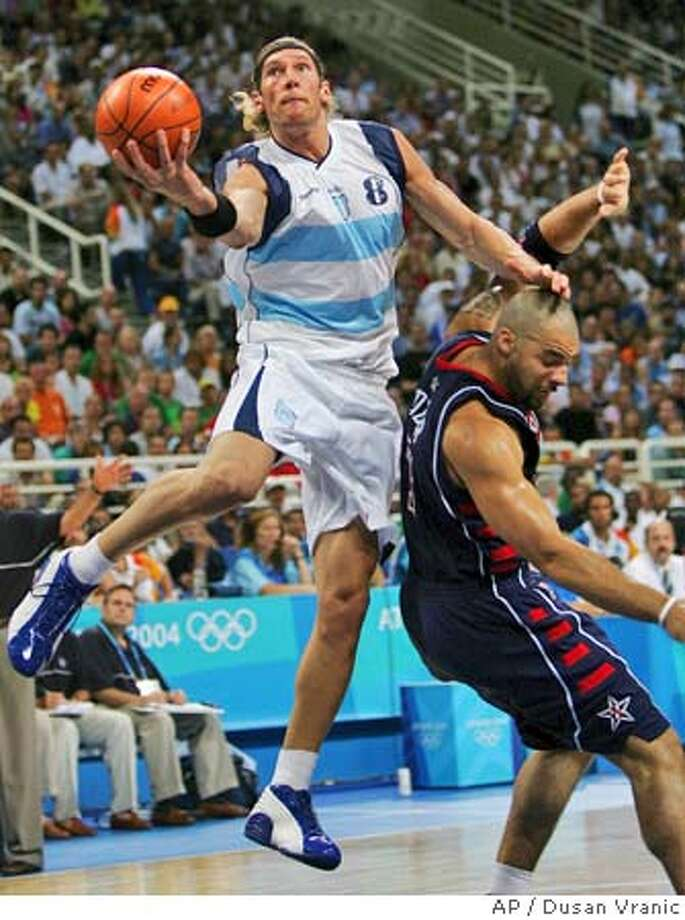Argentina's Walter Herrmann (8) goes over the head of the USA's Carlos Boozer to make a shot in the second period of their game at the Olympic Indoor Hall during the 2004 Olympics in Athens, Greece on Friday, Aug. 27, 2004. (AP Photo/Dusan Vranic) Photo: DUSAN VRANIC