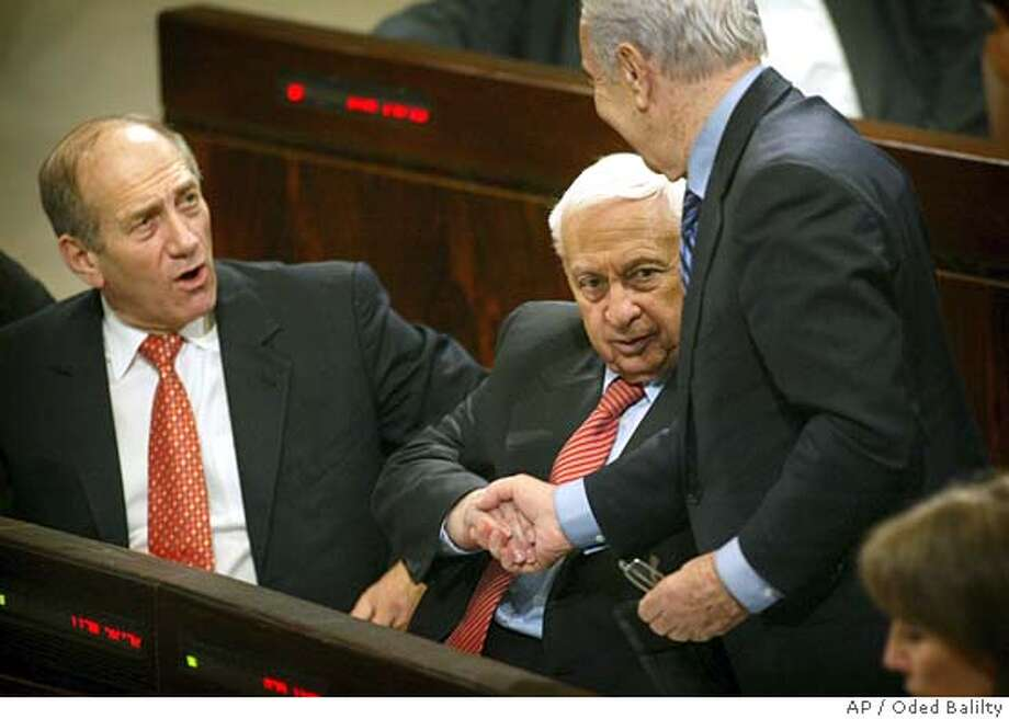 Israeli Prime Minister Ariel Sharon, center, is congratulated by Vice Premier Shimon Peres as Vice Premier Ehud Olmert, left, looks on after the final approval by Israel's parliament of Sharon's plan to withdraw from the Gaza Strip and four West Bank settlements in Jerusalem, Wednesday Feb. 16, 2005. Israel's parliament gave final approval Wednesday to the plan in a 59 to 40 vote that also approved a bill to compensate the 9,000 settlers who will be affected by the withdrawal. (AP Photo/Oded Balilty) Photo: ODED BALILTY