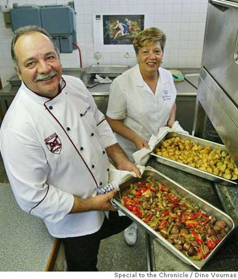 olychef21f.JPG 8/20/04  Antonis Evangelinos of Athens and Terri Moreman of the US are the cooks for the US Olympic teams, working in the kitchens and cafeteria of the American College of Greece in Athens. They are cooking sausage with peppers and roasted potatoes. Dino Vournas/ Special To The Chronicle