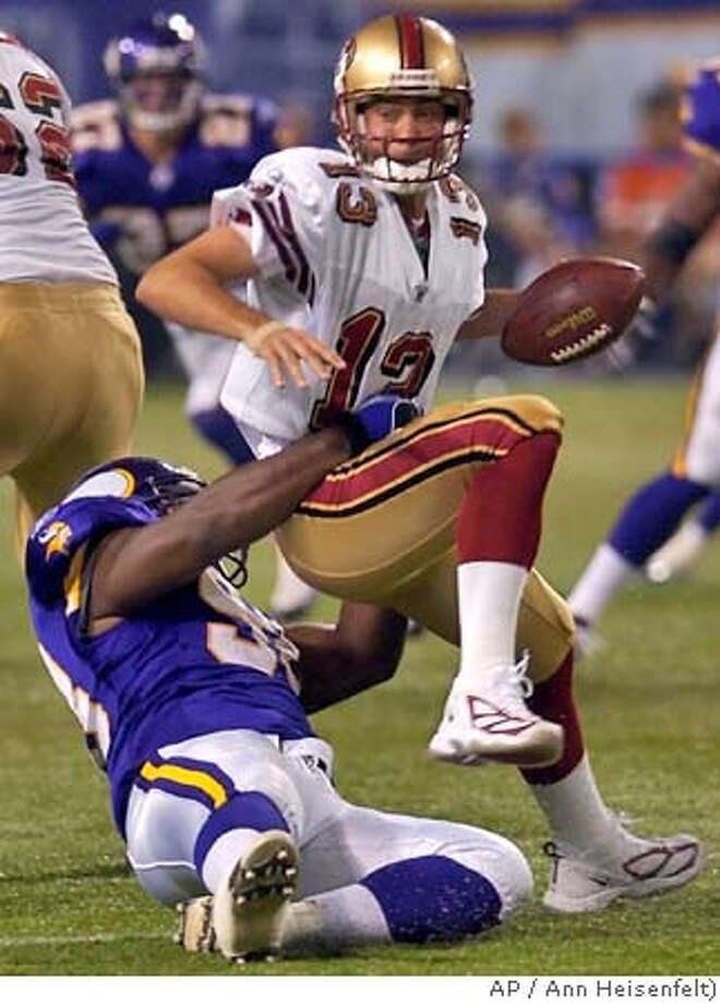 Minnesota Vikings defensive end Darrion Scott, bottom, sacks San Francisco 49ers quarterback Tim Rattay (13) for a 5-yard loss during the second quarter of preseason play in Minneapolis, Friday, Aug. 27, 2004. (AP Photo/Ann Heisenfelt) Photo: ANN HEISENFELT