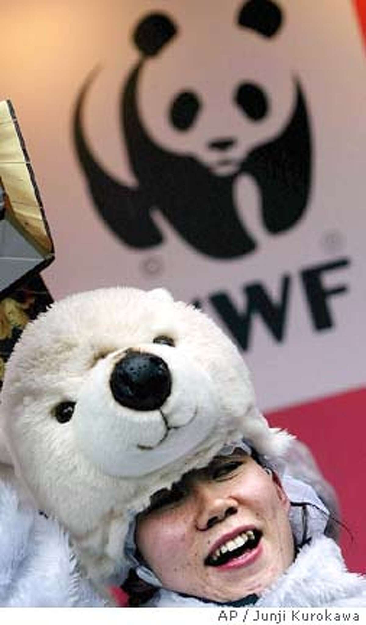 An activist in a polar bear outfit speaks out to the public about the Kyoto global warming pact in a downtown street in Tokyo, Wednesday, Feb 16, 2005. The Kyoto global warming pact took effect Wednesday seven years after it was negotiated, requiring dozens of industrial nations to reduce emissions of
