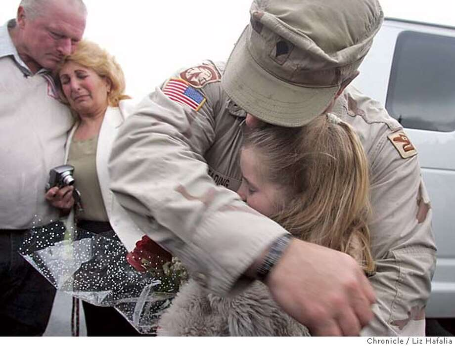 Parents Randy and Victoria Keading (left) watch their son Leroy Keading, 38 years old, as he hugs his 10 year old daughter, Ashley Keading. He was away in Iraq for about a year. Fourteen members of the national guard were reunited withtheir families today. They were driven in from Camp Roberts and arrived at 3:20pm. Shot in Santa Rosa on 2/15/05. Photo: Liz Hafalia