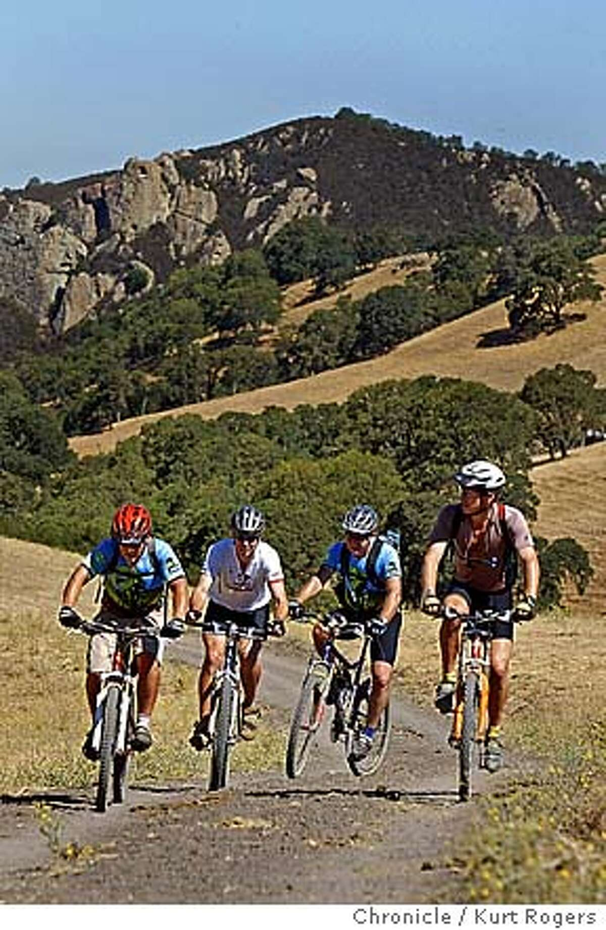 """Shaun Reid 34, Sheve Johnson 45, Eric Muhler 54 and Mike Mccormack Ride up Briones-Mt Diablo Trail with Castle Rock 972"""" in the background . there are a lot more mtn. bike riding opportunities in the bay area than just marin. mike mccormack, a member of the bicycle council and the writer for this story, will meet you with some members of the bicycle council mountan-kr0161.JPG 8/7/04 in Alamo,CA. Kurt Rogers/The Chronicle"""