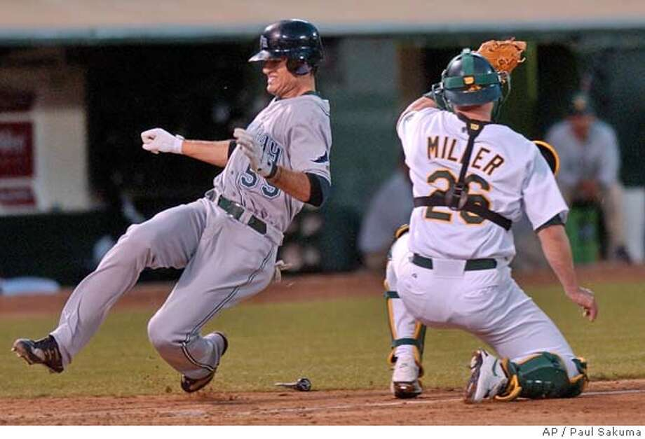 Tampa Bay Devil Rays' Jorge Cantu scores past Oakland Athletics catcher Damian Miller on a single by Julio Lugo in the third inning Friday, Aug. 27, 2004, in Oakland, Calif. (AP Photo/Paul Sakuma) Photo: PAUL SAKUMA