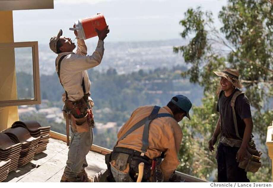 HOTWEATHER0037_LI.JPG Moses Rojas from Oakland working for Dunn Construction also of Oakland takes a drink during roofing of a new home on Skyline Blvd. Moses and his co-workers wear two and three layers of shirts to insulate them from the 90-degree heat. By Lance Iversen/San Francisco Chronicle Photo: Lance Iversen