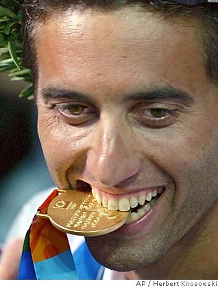 Israel's Gal Fridman bites his gold medal after the Men's Mistral windsurfer sailing event at the 2004 Olympic Games in Athens, Greece, Wednesday Aug. 25, 2004. Fridman won the first gold medal for Israel at the Olympic Games ever. (AP Photo/Herbert Knosowski) Photo: HERBERT KNOSOWSKI