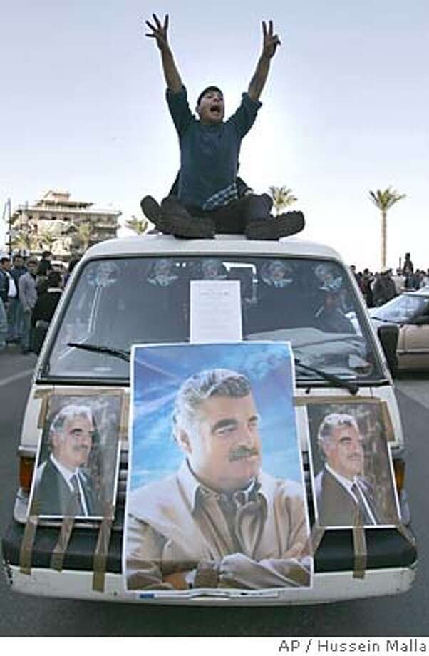 Supporters of slain former Lebanese Prime Minister Rafik Hariri ride through the streets of Beirut, Lebanon Tuesday, Feb. 15, 2005. Hariri was killed in a massive bomb blast Monday raised fears that the country might revert to the political violence of the 1975-90 civil war. (AP Photo/Hussein Malla) Ran on: 02-16-2005  Supporters of Rafik Hariri, the former Lebanese prime minister killed in a huge bomb blast, pay their respects on Beirut's streets. Photo: HUSSEIN MALLA