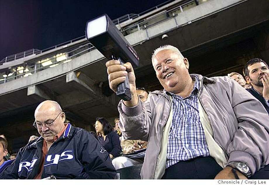 Story on wine at the Oakland A's coliseum. Photo of Detroit Tigers scout, Tom Hinkle, with a radar gun at the pitchers. He also runs a winery in Paso Robles. The man to the left is Stan Williams, scout for the Tampa Bay Devil Rays. The man sitting just over Tom Hinkle's shoulder to the right is Mark Ramirez, an A's fan. Event on 8/14/04 in Oakland. Craig Lee / The Chronicle Photo: Craig Lee