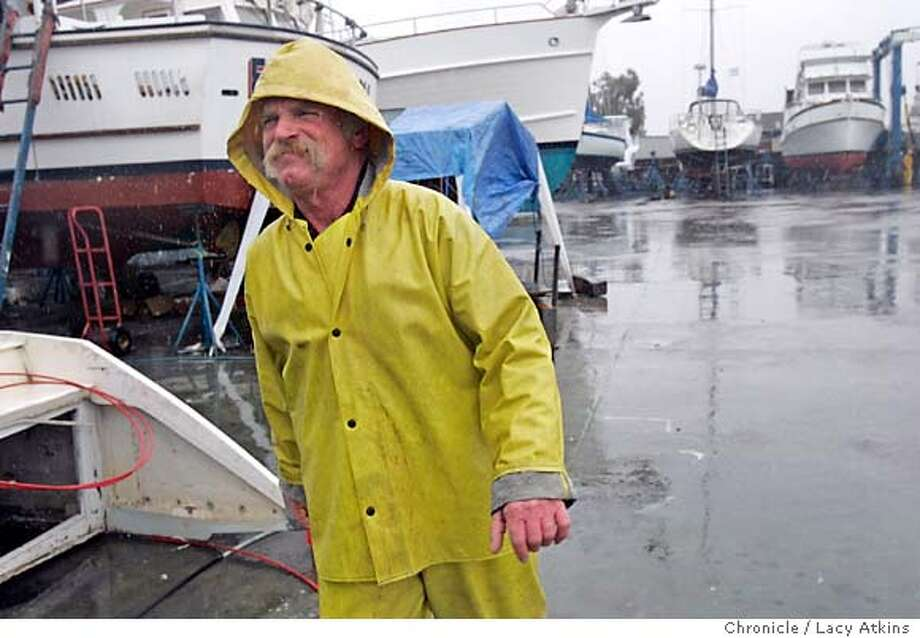 Fernondo Medeiros walks through the Anderson Boat Yard to retrieve another boat as he works rain or shine hauling boats out of the water and moving them with a marine travelift at the Anderson Boat Yard in Sausalito, Feb.15, 2005.  Alberto Garcia washes the particles off boats with a power washer.  Photographer Lacy Atkins / San Francisco Chronicle Photo: LACY ATKINS