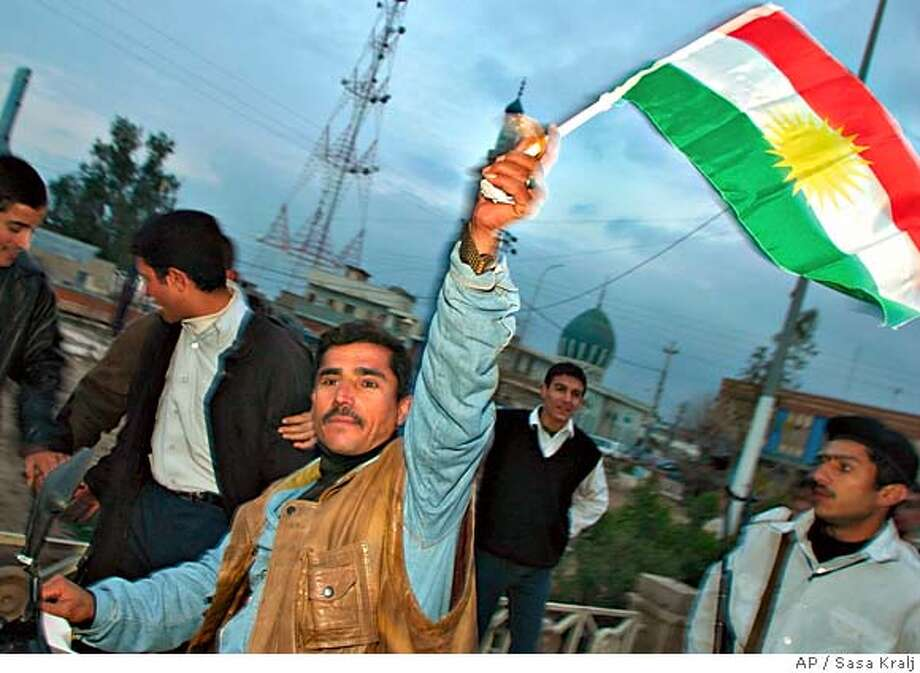 An unidentified Kurdish supporter waves a Kurdish flag as he runs through the streets despite a curfew, celebrating a strong electoral result for the Kurds, in Kirkuk, in the northern Kurdish area of Iraq Sunday, Feb. 13, 2005, after results for the Iraqi general election were announced. Iraq's majority Shiite Muslims won nearly half the votes in the nation's landmark Jan. 30 election, but will have to form a coalition in the 275-member National Assembly with the other top vote-getter - the Kurds and Prime Minister Ayad Allawi's list. (AP Photo/Sasa Kralj) Ran on: 02-14-2005  In Kirkuk, a Kurd celebrates election results that will give the Kurdish people a strong voice in the new Iraqi government. Photo: SASA KRALJ