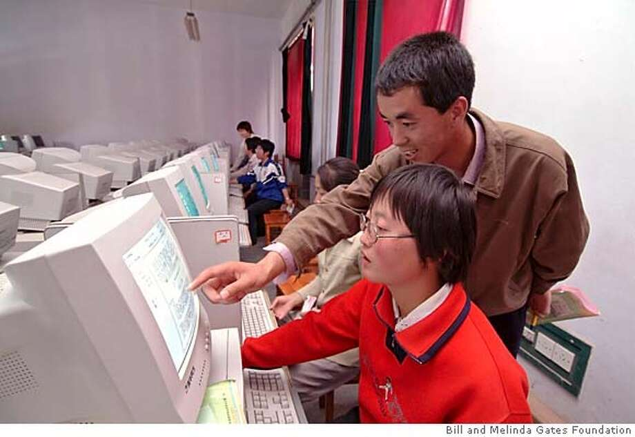 slug: CHINA2  Student(sitting) and teacher(standing)work in computer room at HuiNing High School.
