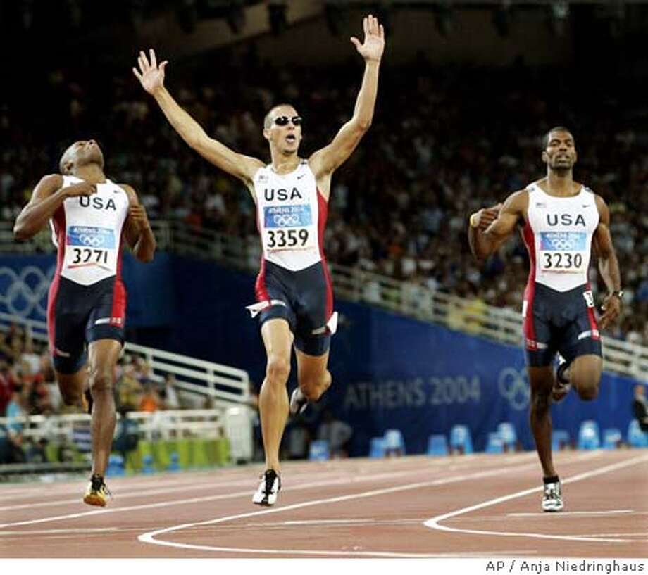Jeremy Wariner, of the United States, center, celebrates as his wins the gold medal in the 400-meter final ahead of compatriot Otis Harris, left, and Derrick Brew, right, at the Olympic Stadium during the 2004 Olympic Games in Athens, Monday, Aug. 23 2004. Harris won the silver, Brew won bronze. (AP Photo/Anja Niedringhaus ) Photo: ANJA NIEDRINGHAUS