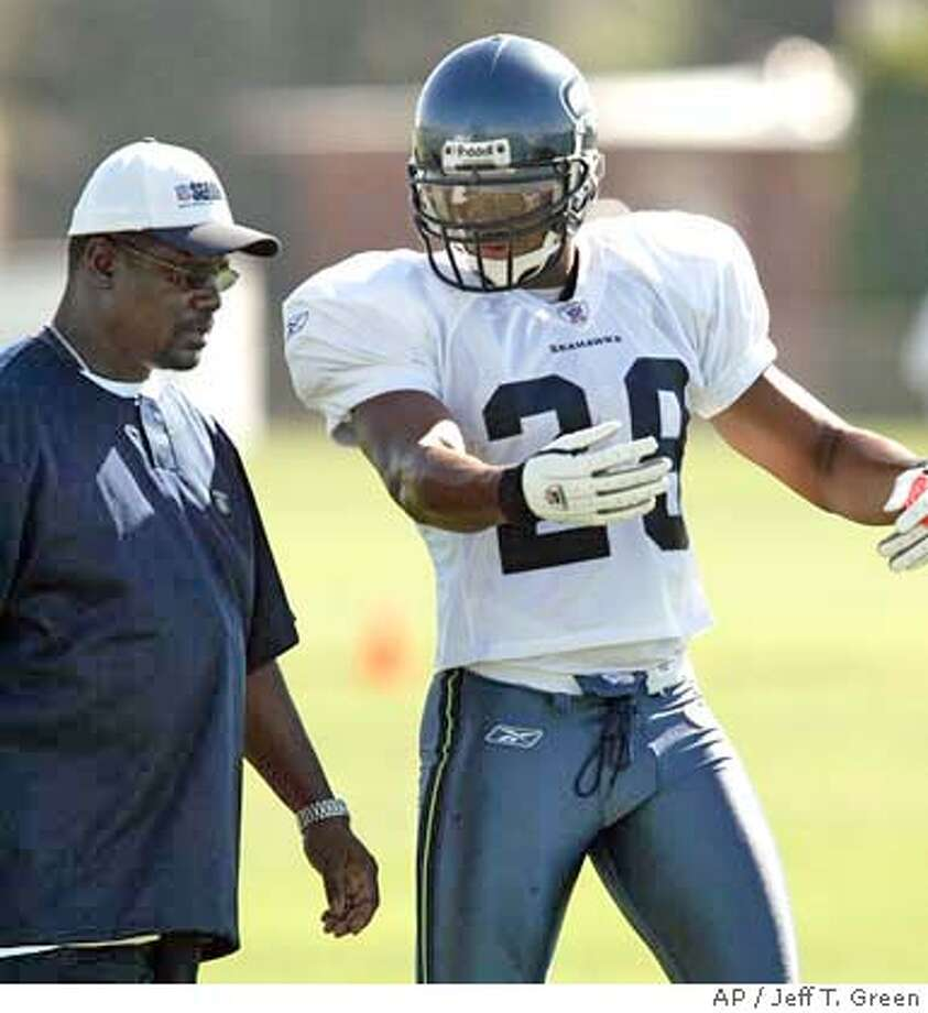 Seattle Seahawks strong safety Michael Boulware, right, talks with defensive coordinator Ray Rhodes, left, during drills at the team's training camp in Cheney, Wash., Thursday, Aug. 12, 2004. (AP Photo/Jeff T. Green) 1 OF 2 Photo: JEFF T. GREEN