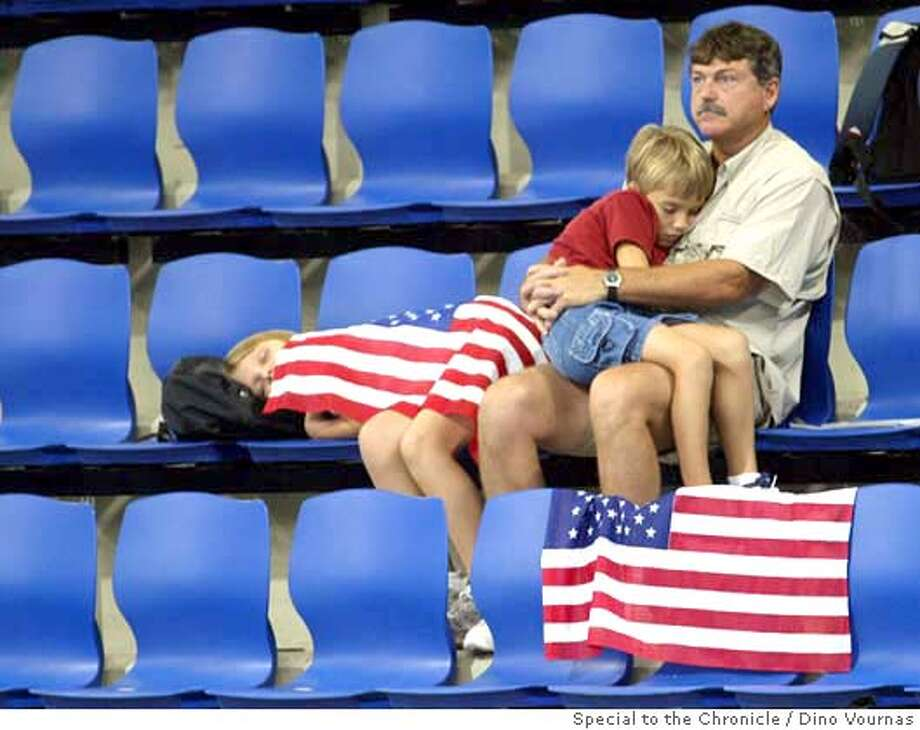 24olywrestling4.jpg 8/23/04  The early start time was probably too much for this family watching the semi-finals of the women's wrestling competition at the Athens Olympics, Ano Liossa Olympic Hall.  Note: Sorry, no ID. Dino Vournas / Special To The Chronicle