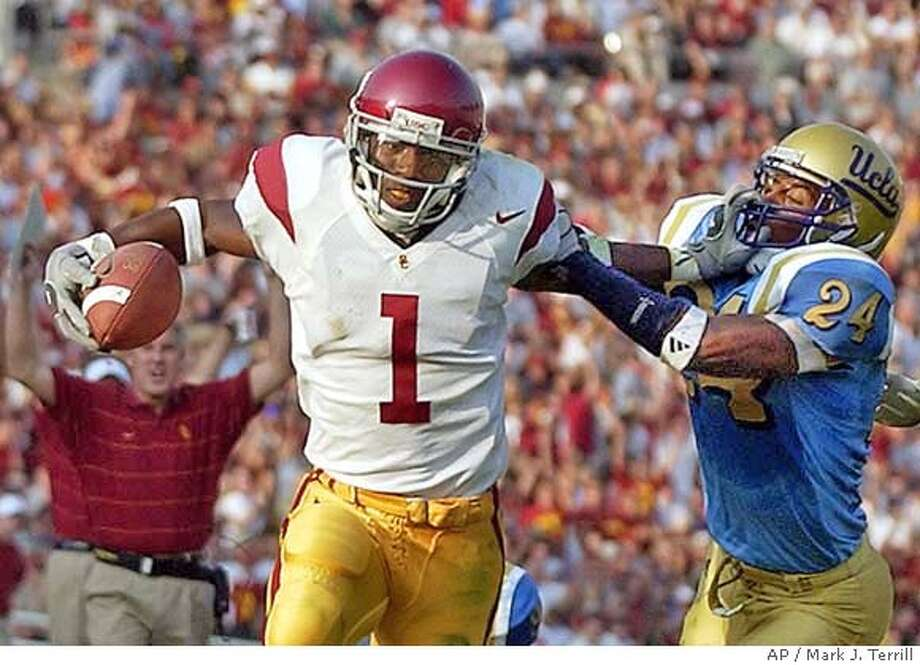 University of Southern Califonia's Mike Williams fends off UCLA's Ben Emanuel ll as USC head coach Pete Carroll, lower left, reacts during the second half, Saturday, Nov. 23, 2002, in Pasadena, Calif. (AP Photo/Mark J. Terrill) Photo: MARK J. TERRILL