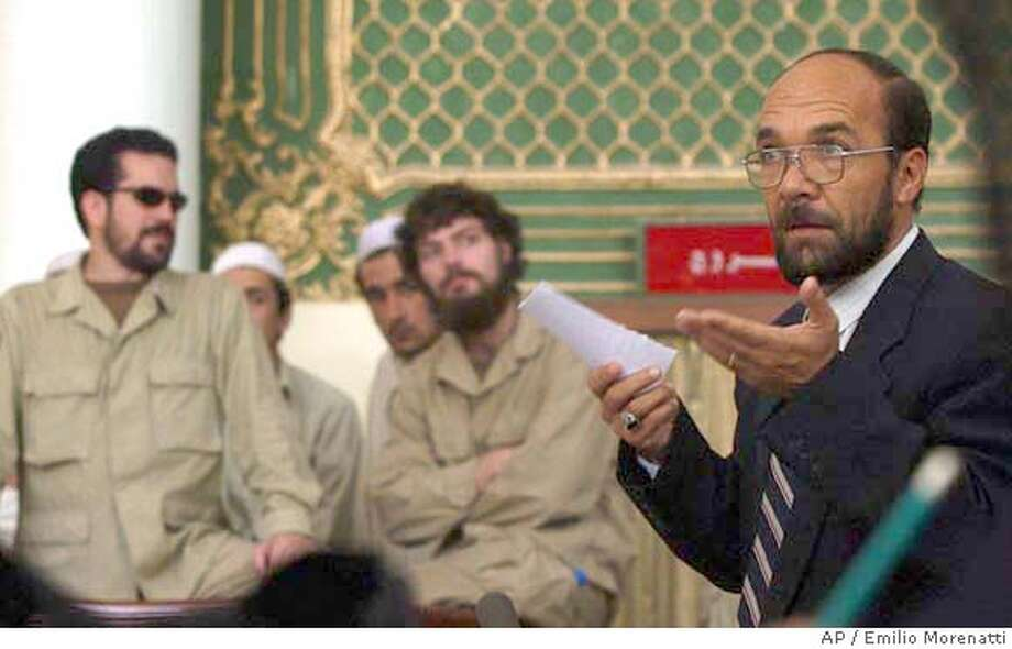 The prosecutor Mohammad Nahim Dawari speaks in front of American Jonathan Keith Idema, left, and Brent Bennett, center, in a court in Kabul on Monday, Aug. 23, 2004. The defense for three American vigilantes accused of torturing a dozen Afghan prisoners showed a court Monday video footage of Afghanistan's former education minister congratulating the group for arresting alleged terrorists. (AP Photo/Emilio Morenatti) Photo: EMILIO MORENATTI