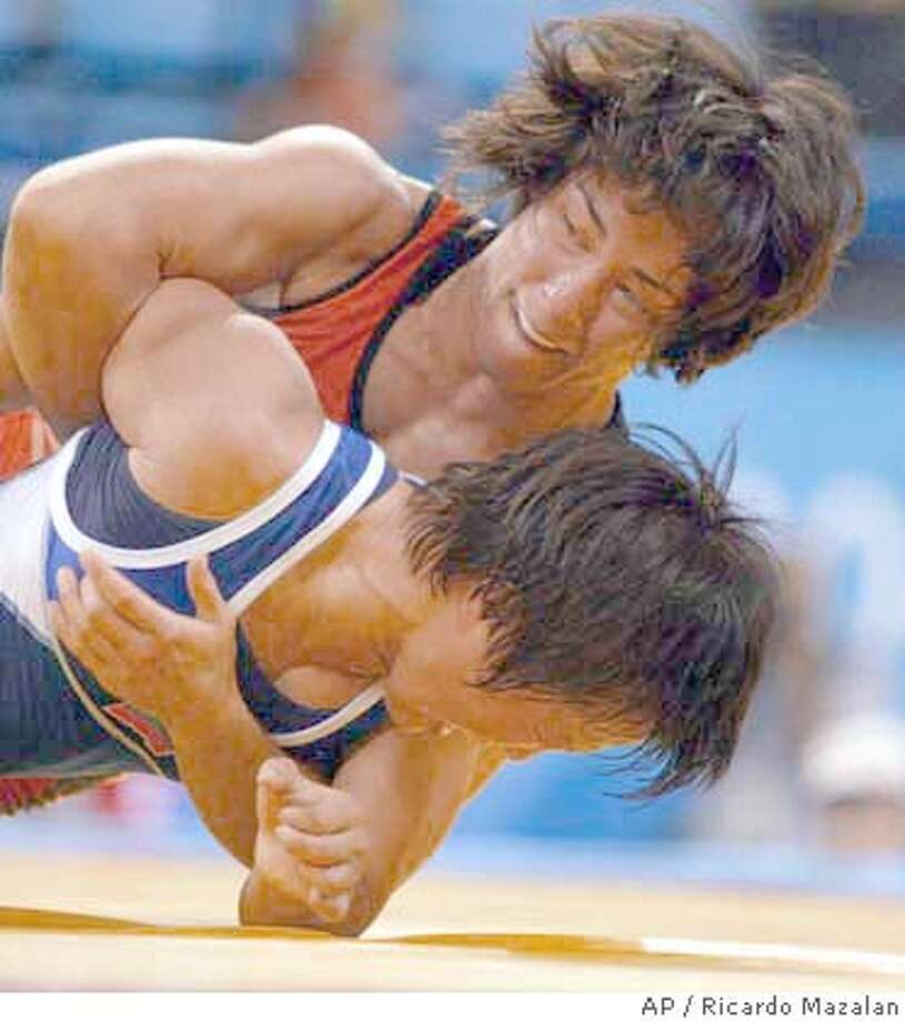 Patricia Miranda, from the United States, top, wrestles Lorisa Oorzhak, from Russia, during the women's freestyle (48kg) wrestling elimination match at the 2004 Olympic Games in Athens, Sunday, Aug. 22, 2004. (AP Photo/Ricardo Mazalan) Photo: RICARDO MAZALAN