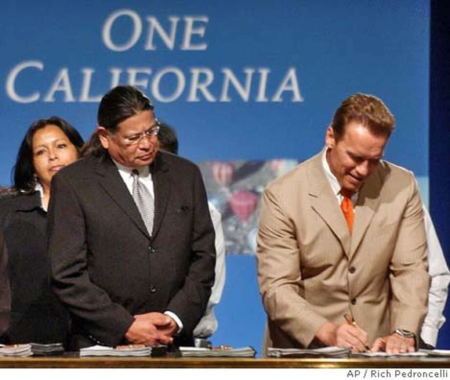 Anthony Pico, chairman of the Viejas Band of Kumeyaay Indians, left, looks on, as Gov. Arnold Schwarzenegger signs an Indian gambling compact with the tribe at a ceremony in Sacramento, Calif., Monday, June 21, 2004. The agreement, reached with five California tribes, allows their tribal casinos to increase the number of slot machines beyond the current 2,000 per tribe cap. In return the tribes will pay the state a licensing fee for each additional slot machine up to $25,000 a machine. The tribes agreed to issue bonds that will bring the state $1 billion to help close this years state budget gap. (AP Photo/Rich Pedroncelli) Ran on: 06-22-2004  Photo caption Ran on: 06-22-2004  Photo caption Ran on: 08-22-2004  Anthony Pico (left) of the Viejas Band of Kumeyaay Indians watches Gov. Arnold Schwarzenegger sign an Indian casino deal in June. Photo: RICH PEDRONCELLI