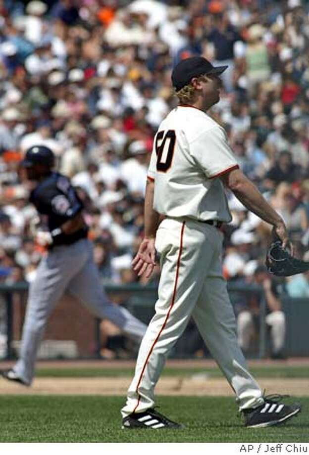San Francisco Giants starting pitcher Brett Tomko, right, walks away from the mound after giving up a three-run home run to New York Mets' Cliff Floyd, rear, who circles the bases in the fifth inning in San Francisco on Saturday, Aug. 21, 2004. The Mets won, 11-9, in 12 innings. (AP Photo/Jeff Chiu) Photo: JEFF CHIU