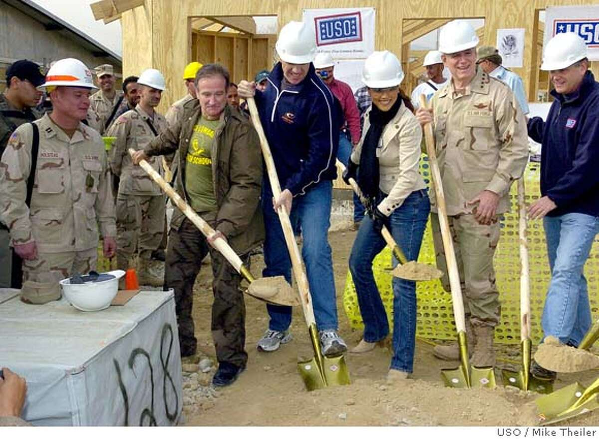 BAGRAM AIR BASE, AFGHANISTAN - DECEMBER 16: In this handout picture from the United Service Organizations, (R-L) USO President and CEO Ned Powell, Chairman of the Joint Chiefs of Staff General Richard B. Myers, model Leeann Tweeden, NFL Hall of Famer John Elway and comedian Robin Williams attend a ceremony for a United Service Organizations (USO) center named in honor of Pat Tillman on December 16, 2004 at Bagram Air Base, Afghanistan. The USO center will honor Tillman, the former Arizona Cardinals star, who left the NFL to join the Army Rangers and was killed in action in Afghanistan earlier this year. (Photo by Mike Theiler/USO via Getty Images) *** Local Caption *** Ned Powell;Richard B. Myers;Leeann Tweeden;John Elway;Robin Williams