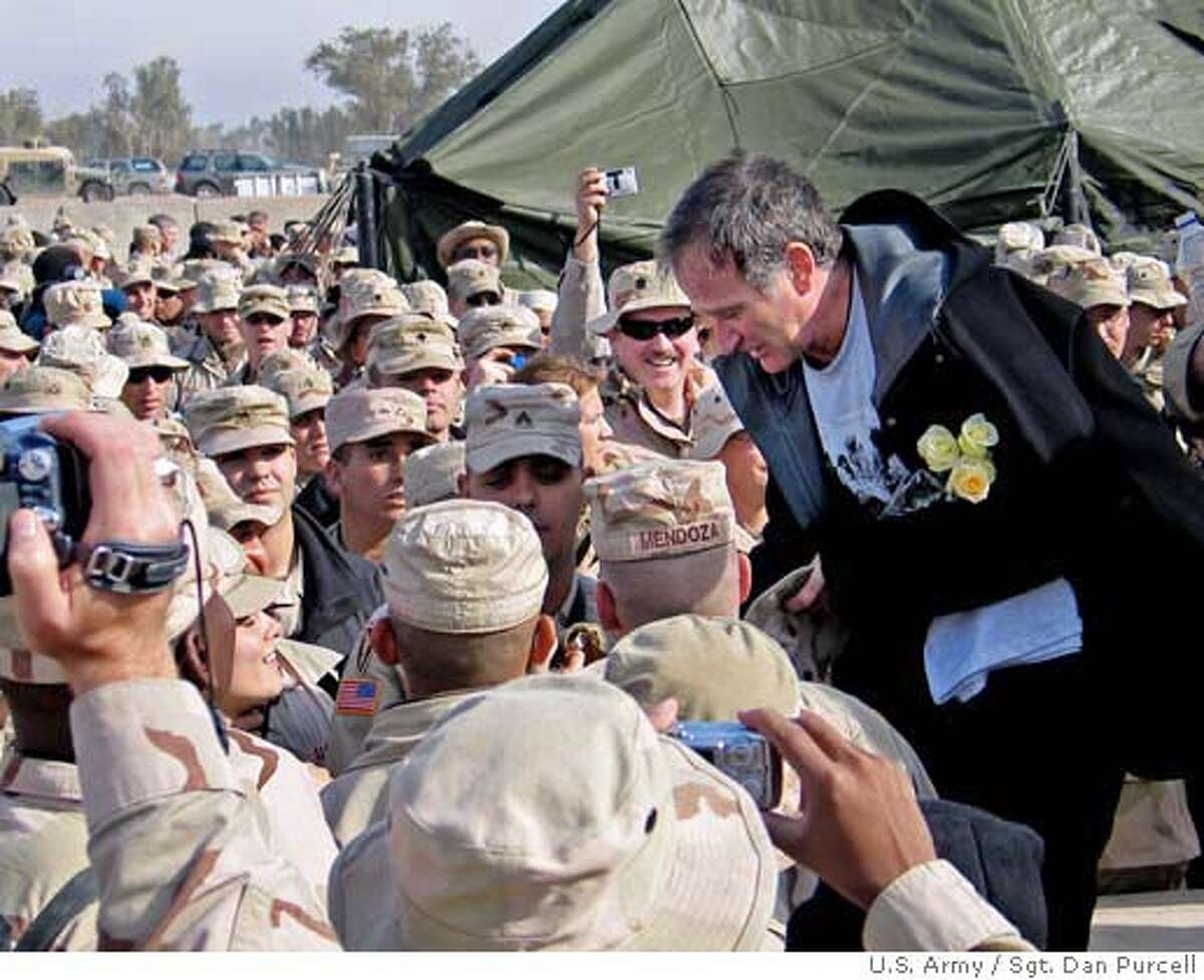 In this image supplied by the Department of Defense, Robin Williams shakes hands and poses for photos with some of the troops gathered at the Camp Liberty Post Exchange in Baghdad, Iraq, during a United Services Organization tour on Tuesday, Dec. 14, 2004. Williams joined Chairman of the Joint Chiefs of Staff Gen. Richard B. Myers, U.S. Air Force, Blake Clarke, John Elway and Leann Tweedon on the USO tour to meet, entertain and thank the deployed troops. (AP Photy/ DOD/ Sgt. Dan Purcell, U.S. Army) Ran on: 12-15-2004 Photo caption Ran on: 02-06-2005