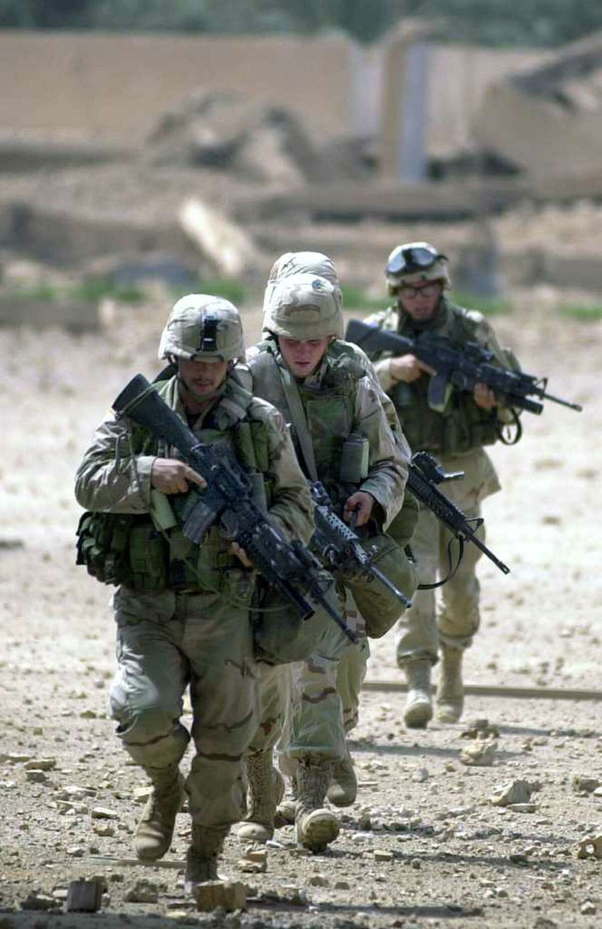 Infantry soldiers run to their position as U.S.troops clear a Special Republican Guard headquarters compound Saturday, April 5, 2003 near Saddam International Airport in Iraq.